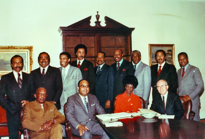 An image of a group of people, four of whom are seated at a table, and nine of whom are standing.