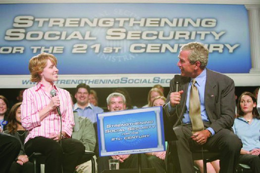 A photo of George W. Bush speaking at an event. The banner behind him says