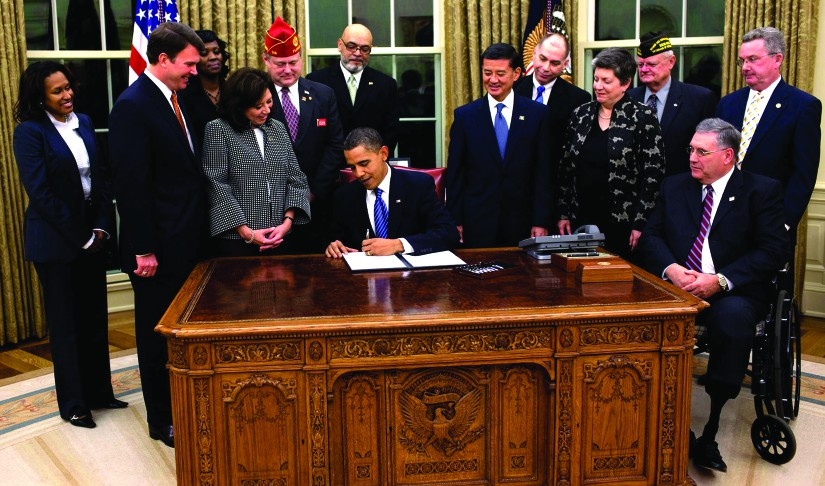 An image of a group of 12 people standing around Barack Obama, who is seated at a desk and signing a piece of paper.