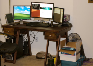 A desk with three computer monitors atop it and a cat sleeping below it.