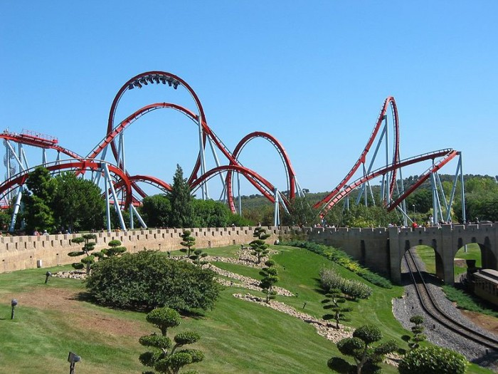 In this figure the Dragon Khan rollercoaster in Spain's Universal Port Aventura Amusement Park is shown. There are mostly curved paths in the rollercoaster. Near to the rollercoaster there is the track of rollercoaster cart under a bridge. There are some trees near the track.