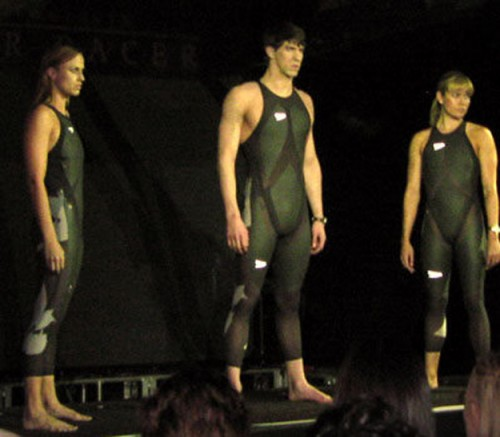 Three swimmers each wearing an L Z R Racer Suit, which is a swimsuit composed of elastane nylon and polyurethane. The seams of the suit are ultrasonically welded to reduce drag.
