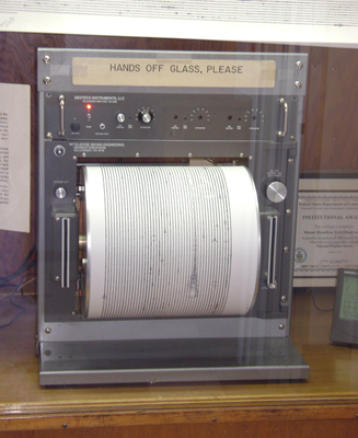 "The figure shows a seismograph put on a wooden table. Its top is labeled as ""Hands off glass, please"". Below it there are some buttons are shown and a paper roller is fitted in the seismograph to print the observation by the machine. On the right and left of the roller, two vertical cable slots are given."