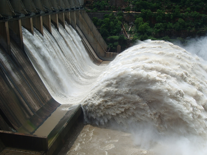 A large volume of water gushes out of the gates of a dam at a hydroelectric facility.