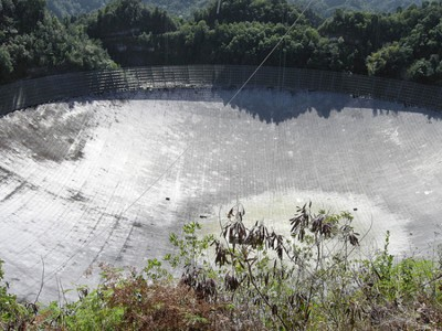 The Figureshows a photograph from above looking into the Arecibo Telescope in Puerto Rico. It is a huge bowl-shaped structure lined with reflecting material. The diameter of the bowl is three times as long as a football field. Trees can be seen around the bowl, but they do not shade the bowl significantly.