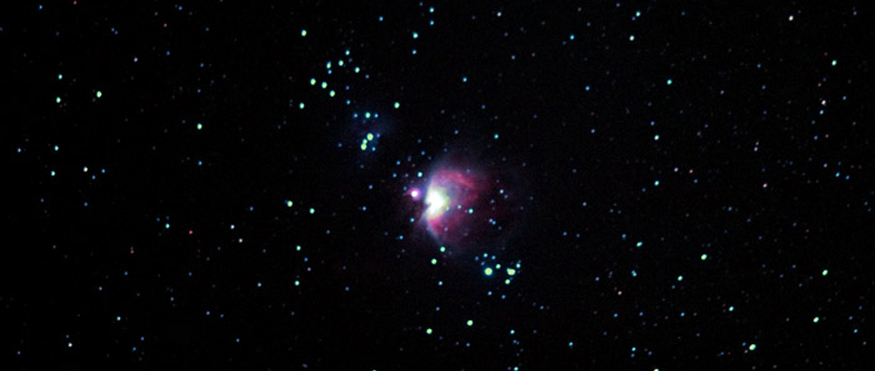 Night sky with bright Orion Nebula cluster in the center amongst the group of stars.