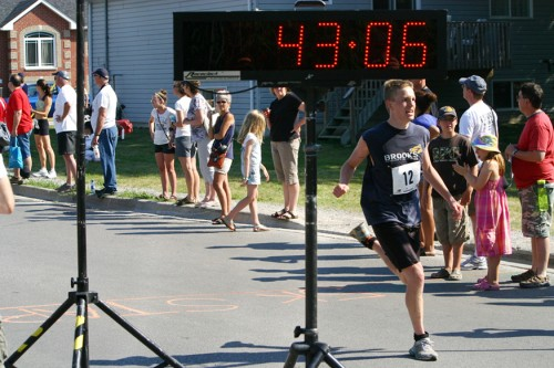A runner crossing a finishing line on a road with a clock showing his finish time.