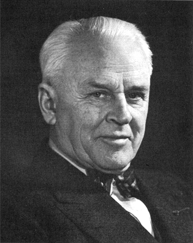 Black and white image of physicist Robert Millikan wearing a jacket and a bow tie.