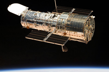The figure shows a satellite in orbit above the glowing atmosphere of the Earth. The satellite is tube shaped and has a cover that is open at one end. It has two solar panels and is covered in what looks like aluminum foil.