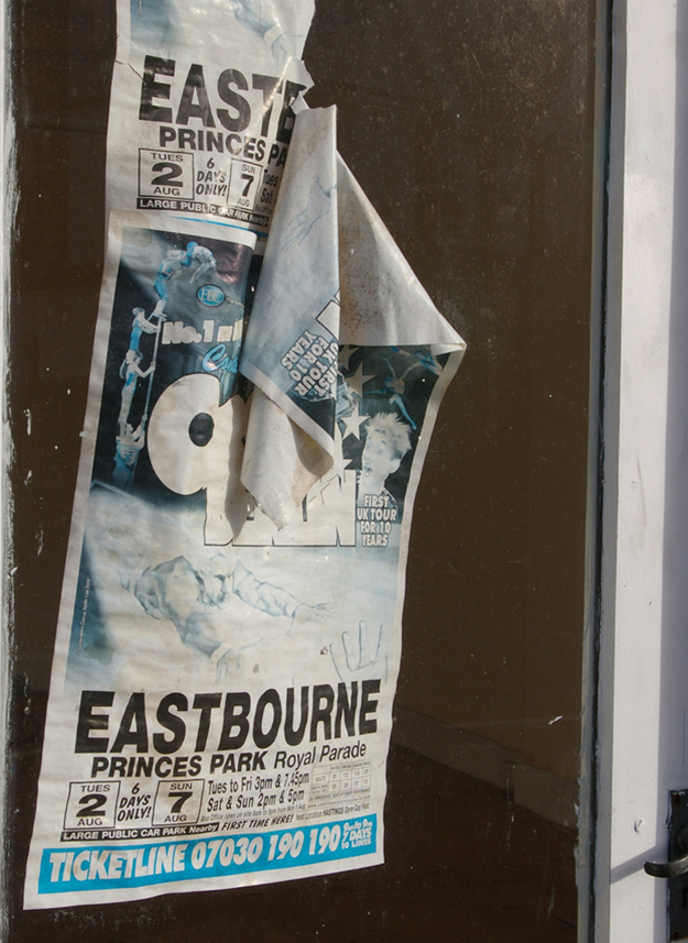 Photograph of a worn-out movie advertisement poster on a wall.