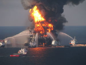 Small ships blast water at an oil rig that is on fire.