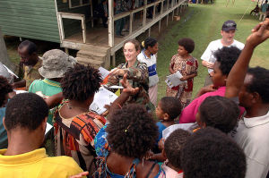 U.S. soldier distributing handouts explaining symptoms of tuberculosis to local residents at Bunabun Health Center in Madang, Papua New Guinea.