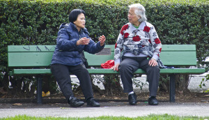 Two people having a conversation on a bench.