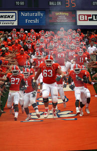 Clemson Tigers football team running in front of cheering fans.