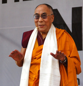 Dalai Lama wearing a white sash and saffron robes, hands outstretched facing down