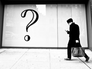 Man walking by question mark on wall