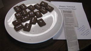 A plate full of cookies with punctuation marks on them.