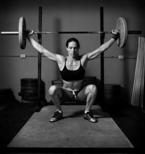 Photograph of female squatting under weight bar