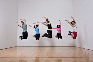 Five people all in the same mid-air jumping pose
