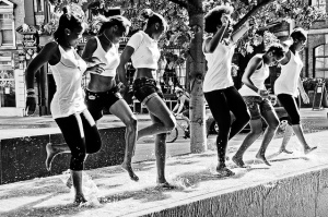 Black and white photo of women dancing in a street