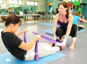 Instructor holding feet of woman using resistance band for sit-ups
