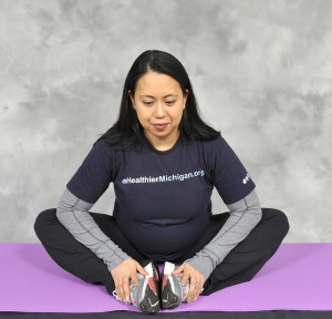 Pregnant woman sitting on floor, stretching