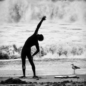 Silhouette of person stretching in front of ocean waves