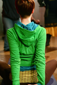 Person in green hoodie stretching arms down behind back