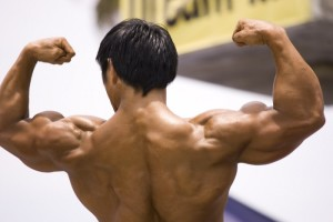 This photograph shows a man flexing his muscles.