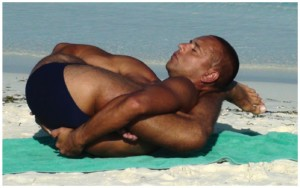 This photo shows a man executing a complicated yoga pose.