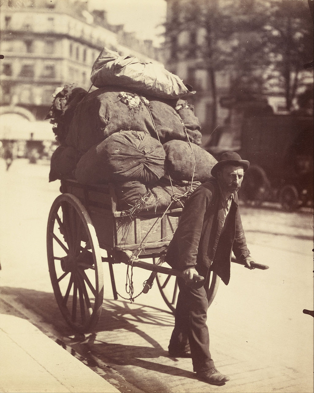 Man on a Paris street pulling a two-wheeled handcart loaded with sacks of old rags