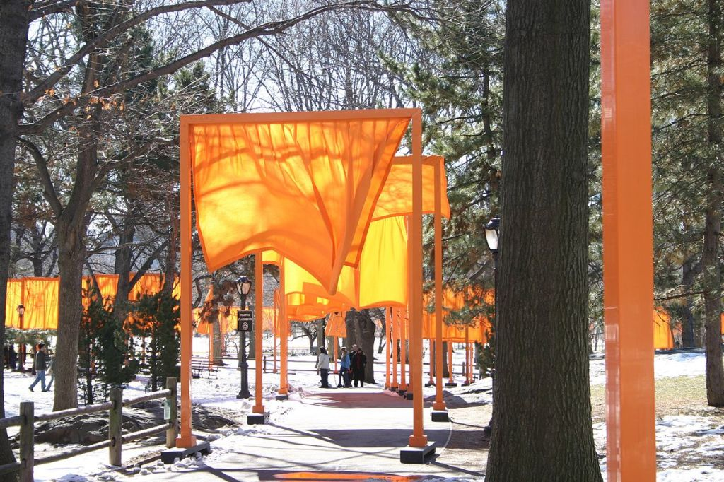 "A series of large orange rectangular arches or ""gates,"" lining the paths of Central Park. Each gate has a sheer, orange piece of fabric hanging beneath it."
