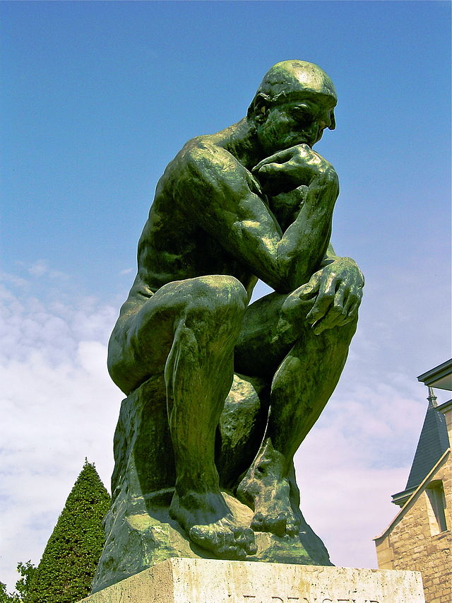 """Photograph of Rodin's """"The Thinker"""" in Paris. The statue is of a man sitting on a rock with his left arm resting on his left leg, and his right arm is bent so that his right elbow touches his left knee and his arm bends so that he can rest his chin on the top of his right hand. He is deep in thought."""