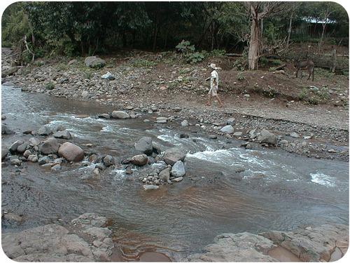 Uma pessoa caminhando ao longo do leito de um rio. Há muitas pedras no leito do rio.