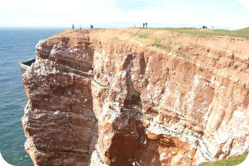 Várias pessoas em pé sobre um enorme penhasco de arenito com vista para o oceano. O arenito tem estrias claras.