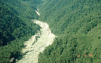 Rio que flui através de uma floresta; o rio é misturado com fragmentos de rocha, fazendo a água parecer cinzenta e grossa.