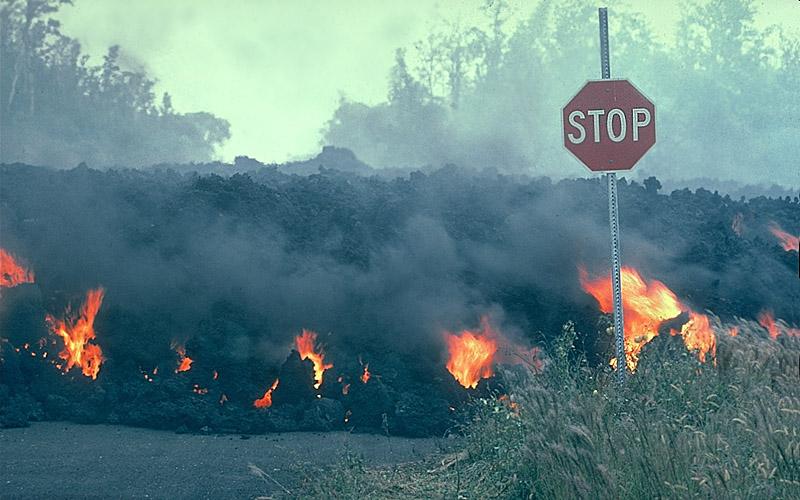 Fluxo de lava com fogo visível movendo-se atrás de um sinal de stop.