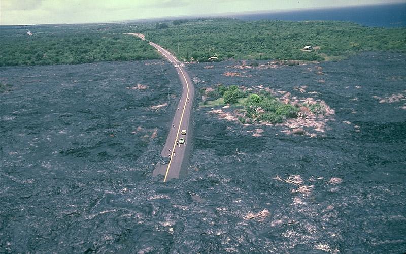 Rodovia completamente cercada e parcialmente coberta de lava. A lava se estende por pelo menos um quilômetro por todos os lados.