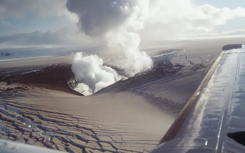 Fotografia tirada de um avião; Há ainda uma enorme nuvem vinda do vulcão.