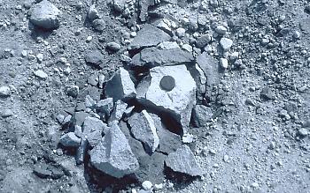 """Bloco Tephra (também chamado de balístico) no chão da cratera do Monte Santa Helena, a cerca de 100 m da cúpula de lava. Esse fragmento de lava foi soprado da cúpula por uma explosão de curta duração causada por (1) uma liberação vigorosa de gás do magma dentro ou abaixo da cúpula; ou (2) por água subterrânea superaquecida """"piscando"""" a vapor. A rocha se quebrou quando aterrissou no chão da cratera."""