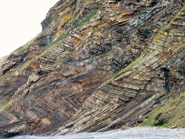 Rock face com padrões de chevron de camadas sedimentares.
