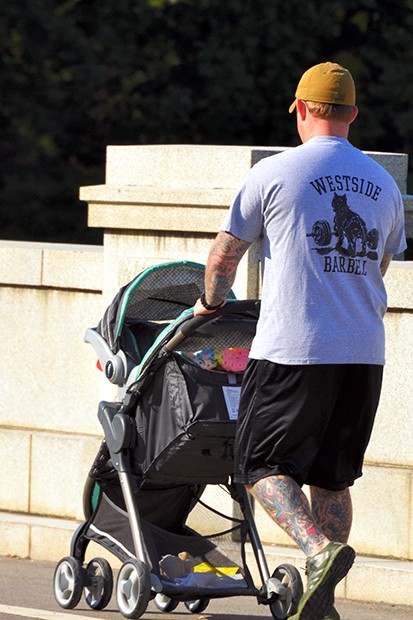 Man with tattooed legs and arms in athletic clothing, pushing a baby stroller.