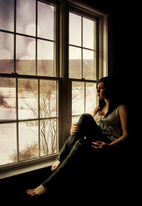 Woman sitting in front of window