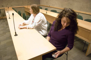 Woman looking at phone under classroom table