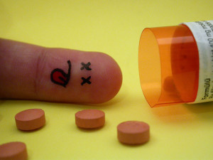 Finger with a dead face drawn on it, next to a spilled pill bottle