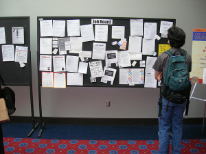 Student standing in front of job bulletin board