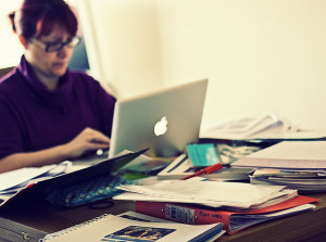 Woman with laptop and table covered in paper and books
