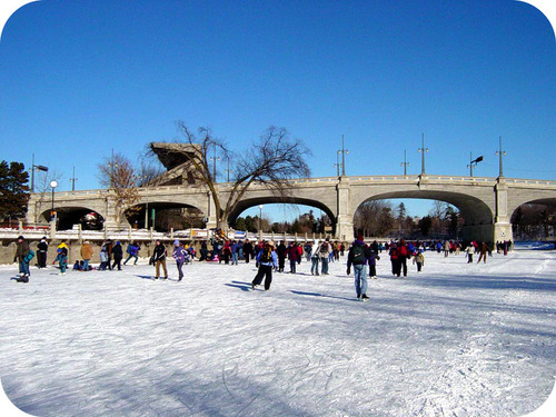 Ice is unique because water expands as it is frozen. Photo of people ice skating under a bridge.