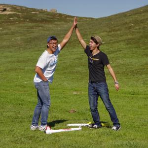 Two men high-fiving outside