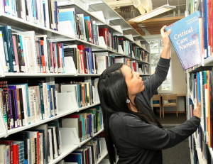 Student pulling book off library shelf